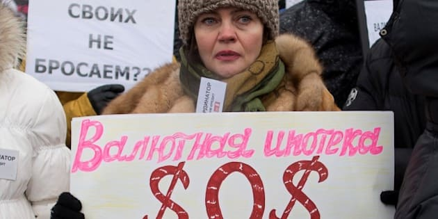 A protester holds a banner reading 'Foreign currency mortgages - SOS' during a rally against the banks and the growth of the dollar in central Moscow on December 28, 2014. With Russia's mortgage industry still in its formative phase, taking out a loan to buy a home is considered risky business. Even before the crisis, interest rates of 10 to 12 percent on foreign currency loans -- and 12 to 14 percent on ruble-denominated mortgages -- mean many Russians will wind up paying double to triple the principal borrowed on 15- to 20-year loans. The group of foreign currency mortgage holders says Russia's financial crisis, exacerbated by falling oil prices and Western sanctions over Ukraine, has transformed their loans into 'financial slavery'. AFP PHOTO / DMITRY SEREBRYAKOV        (Photo credit should read DMITRY SEREBRYAKOV/AFP/Getty Images)