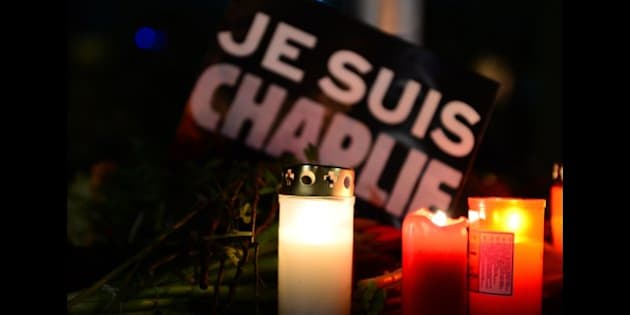 Candles and flowers are placed in front of a poster reading 'I am Charlie' during a spontaneous vigil outside the French embassy on January 7, 2015 in Berlin to express solidarity with employees of the French satirical weekly Charlie Hebdo that has been target of an attack by unknown gunmen. German Chancellor Angela Merkel condemned the 'despicable' attack on Charlie Hebdo that left at least 12 people dead in a condolence letter to President Francois Hollande.       AFP PHOTO / JOHN MACDOUGALL        (Photo credit should read JOHN MACDOUGALL/AFP/Getty Images)