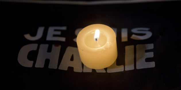 """A candle burns on a sign that reads in French """"I am Charlie"""" during a gathering in solidarity with those killed in an attack at the Paris offices of the weekly newspaper Charlie Hebdo, in Sao Paulo, Brazil, Wednesday, Jan. 7, 2015. Masked gunmen stormed the offices of the satirical newspaper that caricatured the Prophet Muhammad, killing 12 people Wednesday, including the editor, before escaping in a car. It was France's deadliest postwar terrorist attack. (AP Photo/Andre Penner)"""