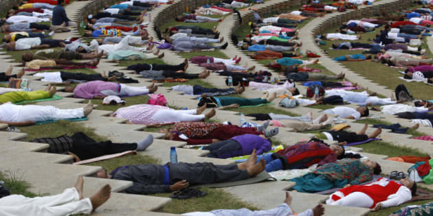 """Yoga enthusiasts lie down after performing Surya Namaskar or sun salutation during """"Yogathon 2014,"""" as part of a countrywide challenge of performing 108 rounds of the sun salutation at the Art of Living headquarters on the outskirts of Bangalore, India, Sunday, Dec. 14, 2014. The United Nations on Thursday declared that June 21 will be observed as the International Day of Yoga. (AP Photo/Aijaz Rahi)"""