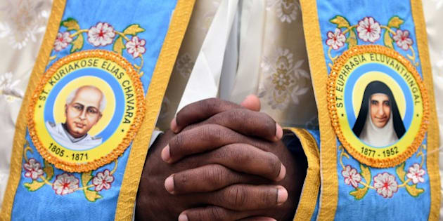An Indian priest prays prior to a canonization mass for Indian priest Kuriakose Elias Chavara, represented at left, and Indian Carmelite nun Euphrasia Eluvathingal, represented at right, to be celebrated by Pope Francis at St Peter's square on November 23, 2014 at the Vatican.  AFP PHOTO / GABRIEL BOUYS        (Photo credit should read GABRIEL BOUYS/AFP/Getty Images)