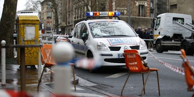 Cordons are seen near a municipal police car at the site of a shooting on the morning of January 8, 2015 in Montrouge, south of Paris. A policewoman and a city employee were seriously hurt on January 8 after a man fired on them with an automatic rifle outside Paris, police said, but no link has yet been established with the deadly magazine attack on January 7. The gunman is still on the run, said Interior Minister Bernard Cazeneuve -- who rushed to the scene -- contradicting information given earlier by a source close to the case, who said the suspect had been detained.  AFP PHOTO / KENZO TRIBOUILLARD        (Photo credit should read KENZO TRIBOUILLARD/AFP/Getty Images)