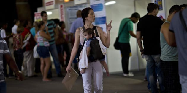 A woman carrying a baby and a resume attends a job fair promoted by the mayor's office to boost employment in the port area currently under renovation in Rio de Janeiro, Brazil, on Monday, Nov. 10, 2014. Brazil's jobless rate for the second-quarter of 2014 fell to 6.8 percent from 7.4 percent in 2013, according to the latest unemployment report from the  Brazilian Institute of Geography and Statistics. Photographer: Dado Galdieri/Bloomberg via Getty Images