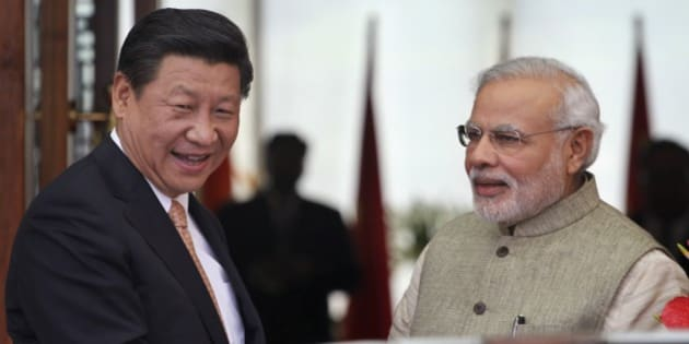 Indian Prime Minister Narendra Modi, right, welcomes Chinese President Xi Jinping, upon his arrival at a hotel in Ahmadabad, India, Wednesday, Sept. 17, 2014. Xi landed in Modi's home state of Gujarat on Wednesday for a three-day visit expected to focus on India's need to improve worn out infrastructure and reduce its trade deficit. (AP Photo/Ajit Solanki)