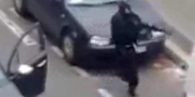Masked gunman fire their weapons outside the  French satirical newspaper Charlie Hebdo's office, in Paris, Wednesday, Jan. 7, 2015. Paris residents captured chilling video images of two masked gunmen shooting a police officer after an attack at a French satirical newspaper. In the video, the gunmen armed with assault rifles are seen running up to an injured police officer, who lies squirming on the ground. The police officer raises his hands up before one of the assailants shoots him in the head at a close range.  (AP Photo) NO SALES