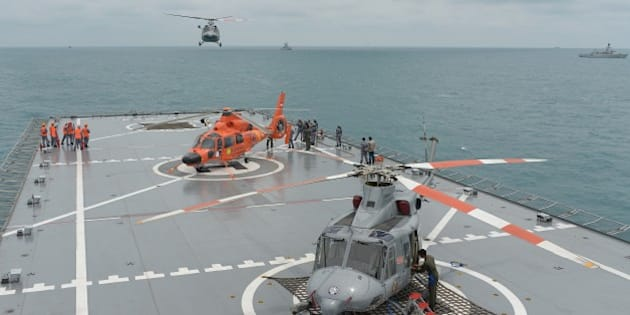 A navy helicopter arrives on the Indonesian navy vessel KRI Banda Aceh, close to area where search teams located the tail of AirAsia QZ8501 in the Java sea on January 8, 2015. Elite Indonesian military divers battled strong currents on Thursday in an effort to reach the submerged tail of crashed AirAsia Flight QZ8501 in the hopes of finding crucial black box data recorders. AFP PHOTO / POOL / ADEK BERRY        (Photo credit should read ADEK BERRY/AFP/Getty Images)