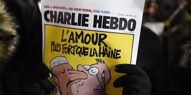A man holds a cartoon as people gather on Union Square January 7, 2015 in New York in memory of the victims of the attack on the offices of the satirical weekly Charlie Hebdo in Paris.   US President Barack Obama condemned the 'cowardly, evil' assault on a French satirical newspaper that left 12 dead, pledging US assistance to Paris to bring the attackers to justice.   AFP PHOTO / DON EMMERT        (Photo credit should read DON EMMERT/AFP/Getty Images)