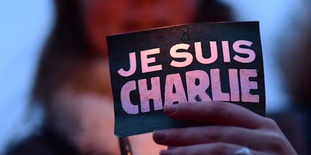 A woman holds a sign reading 'Je suis Charlie' (I am Charlie) during a gathering in Brussels on January 9, 2015 to pay tribute to the victims of a deadly attack on the Paris headquarters of French weekly Charlie Hebdo. Elite commandos units killed the two suspects in the Charlie Hebdo massacre during a simultaneous assault on the building they were holed up in and on a Paris Jewish supermarket, freeing hostages at both sites. AFP PHOTO / EMMANUEL DUNAND        (Photo credit should read EMMANUEL DUNAND/AFP/Getty Images)