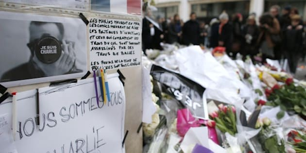 People leave messages and flowers outside the offices of the French satirical newspaper Charlie Hebdo in Paris on January 10, 2015, a day after four people were killed at the Jewish supermarket by an Islamist gunman during a hostage-taking. French forces were on January 10 frantically hunting for Islamist gunman Amedy Coulibaly's 26-year-old girlfriend, Hayat Boumeddiene, as the country mourned 17 dead in three blood-soaked days, hours after a dramatic end to twin sieges that also resulted in the death of two brothers who had killed 12 at the offices of the Charlie Hebdo magazine on January 7. AFP PHOTO / THOMAS SAMSON        (Photo credit should read THOMAS SAMSON/AFP/Getty Images)