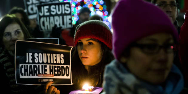 People gather to pay to pay tribute to victims of the terrorist attack against the French satirical weekly Charlie Hebdo, Friday, Jan. 9, 2015, at JFK Plaza, commonly known as Love Park, in Philadelphia. On Wednesday, masked gunmen stormed the Paris offices  of the weekly newspaper that caricatured the Prophet Muhammad, killing at least 12 people, including the editor. (AP Photo/Matt Rourke)