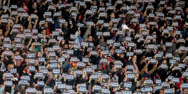 Guingamp's supporter hold signs reading 'Je suis Charlie' (I am Charlie) to pay tribute to the victims of the Charlie Hebdo attack during the French L1 football match between Guingamp and Lens at the Roudourou stadium in Guingamp, western France, on January 10, 2015.  AFP PHOTO / FRED TANNEAU        (Photo credit should read FRED TANNEAU/AFP/Getty Images)