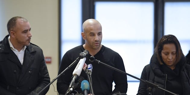 Malek Merabet (C), the brother of Ahmed Merabet, the policeman who was killed in the attacks at the offices of the Charlie Hebdo magazine on January 7, talks during a press conference in Livry-Gargan, northern Paris suburb, on January 10, 2015 with Ahmed's brother-in-law Lotfi Mabrouk (L), and Ahmed's partner Morgane. French forces were on January 10 frantically hunting for Islamist gunman Amedy Coulibaly's 26-year-old girlfriend, Hayat Boumeddiene, as the country mourned 17 dead in three blood-soaked days, hours after a dramatic end to twin sieges that also resulted in the death of two brothers who had killed 12 at the offices of the Charlie Hebdo magazine on January 7. More than 200,000 people took to streets in France on January 10 to show their solidarity after three days of bloody attacks which killed 17 victims at the hands of Islamic extremists, according to a tally of various demonstrations.   AFP PHOTO / MARTIN BUREAU        (Photo credit should read MARTIN BUREAU/AFP/Getty Images)