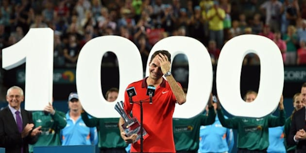 Roger Federer of Switzerland reacts as he celebrates the 1000th victory of his career after beating Milos Raonic of Canada in the men's single final of the Brisbane International tennis tournament in Brisbane on January 11, 2015. AFP PHOTO / Saeed KHAN