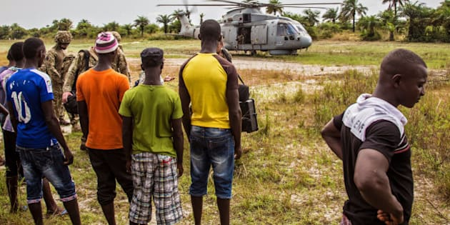 Local residents look at a British Navy helicopter after it made a food drop on Sherbro Island, Sierra Leone, Sunday, Dec. 7, 2014. The WFP, World Food Program and British Military took part in a three day food distribution effort for local residents on the remote Sherbro Island, where the Ebola virus has prevented people from farming, fishing or gathering food. (AP Photo/Michael Duff)