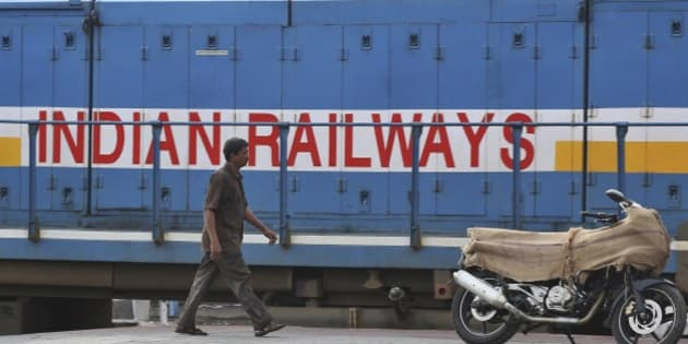 An Indian man walks in front of a train as a motorcycle being transported is kept on a platform at the Secunderabad railway station in Hyderabad, India, Monday, July 7, 2014. India on Tuesday is expected to announce the budget for the national railways system, which is one of the world's largest and serves 23 million passengers a day. (AP Photo/Mahesh Kumar A.)