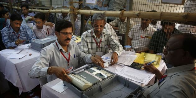 Election officials count votes at a counting station in New Delhi, India, Friday, May 16, 2014. India's main Hindu nationalist party was making early gains Friday as officials began counting votes following the country's massive national election, with the opposition looking to end the ruling Congress party's decade-long reign. The Election Commission was expected to announce the results later in the day. (AP Photo/Manish Swarup)