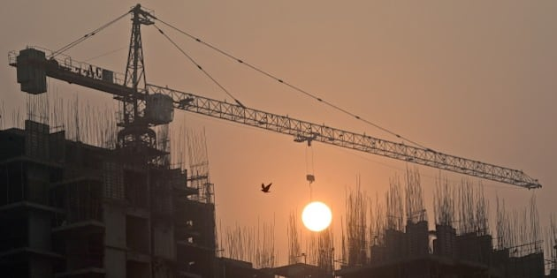 Sun rises over an under-construction apartment building on the outskirts of New Delhi early November 7, 2014.   In the first Japanese entry into the Indian property market, Tama Homes announced November 5,  the construction of 12-18 projects at an investment of some 975 million USD in partnership with Singapore's Developer Group, will jointly build three housing projects, including two townships, having about 3,500 housing units, in Ludhiana, Visakhapatnam and Chennai.   AFP PHOTO/ Prakash SINGH        (Photo credit should read PRAKASH SINGH/AFP/Getty Images)