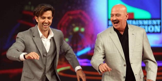 Indian Bollywood actor Hrithik Roshan (L) and his father Rakesh Roshan dance during the annual 'Umang 2015 Mumbai Police Show' in Mumbai on late January 10, 2015. AFP PHOTO / STR        (Photo credit should read STRDEL/AFP/Getty Images)