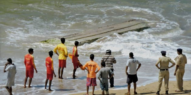 Rescue workers and policemen stand near a boat that capsized, on a beach in Panaji, on the southern coast of Goa state, India, Tuesday, Oct. 28, 2014. The boat taking tourists on a dolphin-sighting trip capsized off India's west coast Tuesday, killing three Russian women, police said. The women were among 10 Russian tourists who chartered the motorboat to follow dolphins more than a kilometer (half mile) off popular Betul beach. A large wave toppled the boat, trapping some of the passengers underneath, police official Nilesh Shirotkar said. (AP Photo/Press Trust of India)