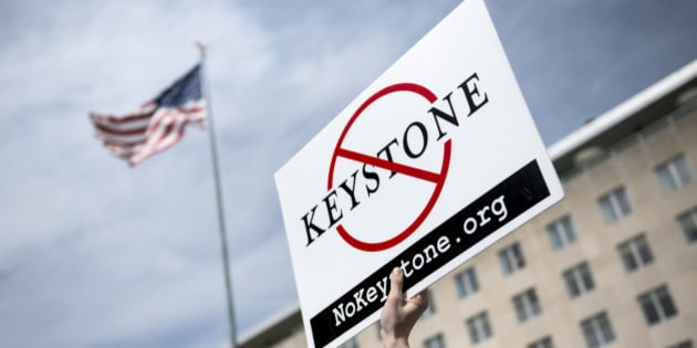 An activist holds up a sign outside the State Department during a protest of the Keystone XL pipeline on March 7, 2014 in Washington. Activists organized by the Energy Action Coalition marched to the State Department to protest the construction of the pipeline which would carry tar sands oil from Canada.   AFP PHOTO/Brendan SMIALOWSKI        (Photo credit should read BRENDAN SMIALOWSKI/AFP/Getty Images)