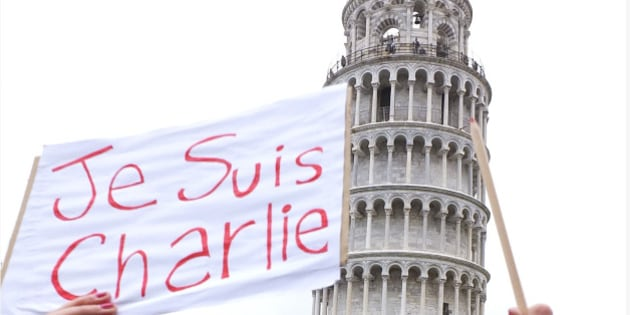 """A woman holds a pencil and a poster reading in French """"I am Charlie"""" during a rally in support of Charlie Hebdo, a French satirical weekly newspaper that fell victim to a terrorist attack in Paris, in front of the Leaning Tower of Pisa, Italy, Sunday, Jan. 11, 2015. Masked gunmen stormed the Paris offices of a weekly newspaper that caricatured the Prophet Muhammad, methodically killing 12 people Wednesday, including the editor, before escaping in a car. (AP Photo/Fabio Muzzi)"""