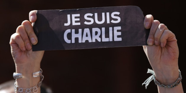"A person holds a sign that reads in French ""I am Charlie"" during a gathering in solidarity with the victims of recent attacks in France at the French Alliance community center in Quito, Ecuador, Sunday, Jan. 11, 2015. People gathered to honor the victims of the shootings at the Paris satirical newspaper Charlie Hebdo and a kosher supermarket in France. Demonstrations were held Sunday in cities around France and around the world. (AP Photo/Dolores Ochoa)"