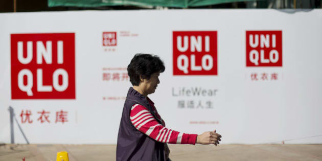 A woman walks past an advertisement for Uniqlo, operated by Fast Retailing Co., at a construction site in the Tianhe district of Guangzhou, Guangdong province, China, on Monday, Nov. 25, 2013. China is proposing the largest package of economic reforms since the 1990s to stoke growth in the worlds biggest emerging market. Photographer: Brent Lewin/Bloomberg via Getty Images