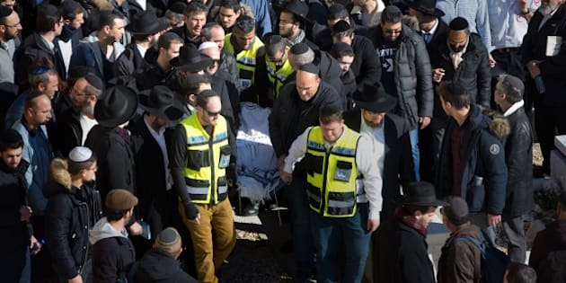Mourners carry the body of a victim at a cemetery in Jerusalem on January 13, 2015 during the funeral of four Jews killed in an Islamist attack on a kosher supermarket in Paris last week. Crowds of mourners were attending the funeral of Yohan Cohen, Philippe Braham, François-Michel Saada and Yoav Hattab after their bodies were flown to Israel from France early in the mourning for burial in the Jewish state. The four Jews were among 17 people gunned down in Paris during three days of bloodshed that convulsed France and sent shock waves through its Jewish community, the third-largest in the world. AFP PHOTO / MENAHEM KAHANA        (Photo credit should read MENAHEM KAHANA/AFP/Getty Images)