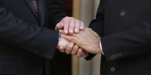 Indian Prime Minister Manmohan Singh, his hands seen on right, shakes hands with Russian Prime Minister Vladimir Putin in New Delhi, India, Friday, March 12, 2010. Putin held talks Friday with Indian leaders during a day's visit that was expected to conclude with the signing of a slew of agreements on defense, space and civil nuclear energy cooperation, Indian officials said. (AP Photo/Manish Swarup)