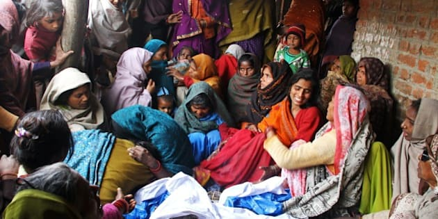 Indian relatives mourn over the bodies (bottom C) of two brothers who died after consuming bootleg liquor at Datli village in Malihabad, Indian's northern Uttar Pradesh state, on January 13, 2015. Twenty seven people have died from alcohol poisoning after drinking the liquor in the northern Indian state of Uttar Pradesh, a report said. More than a hundred patients are receiving treatment with about 10 reported in serious condition, a report said. AFP PHOTO/STR        (Photo credit should read STRDEL/AFP/Getty Images)