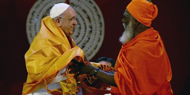 Pope Francis (L) receives a shawl as a gift from Sri Lankan Hindu priest Kurukkal SivaSri T Mahadeva during an inter-religious meeting in the Bandaranaike Memorial International Conference Hall in Colombo on January 13, 2015. Pope Francis urged respect for human rights in Sri Lanka as he began a two-nation Asia tour on the island, bearing a message of peace and reconciliation after a long civil war.  AFP PHOTO / Munir uz ZAMAN        (Photo credit should read MUNIR UZ ZAMAN/AFP/Getty Images)