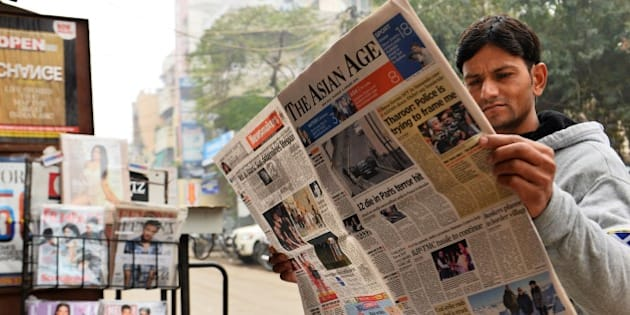 A reader holds up a copy of an English-language Indian newspaper with a front page report on the attack by gunmen on French satirical weekly Charlie Hebdo in Paris that killed 12 people on January 7, at a newsstand in New Delhi on January 8, 2015. A stunned and outraged France began a national day of mourning January 8, as security forces desperately hunted two brothers suspected of gunning down 12 people in an Islamist assault on a satirical weekly, the country's bloodiest attack in half a century. AFP PHOTO / CHANDAN KHANNA        (Photo credit should read Chandan Khanna/AFP/Getty Images)