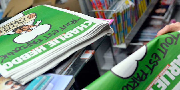 UNSPECIFIED, UNSPECIFIED - JANUARY 14:  A woman buys a copy of the new edition of Charlie Hebdo magazine at a Pigalle newsstand on January 14, 2014 in Paris, France. Three million copies of the controversial magazine have been printed in the wake of last week's terrorist attacks.  (Photo by Aurelien Meunier/Getty Images)
