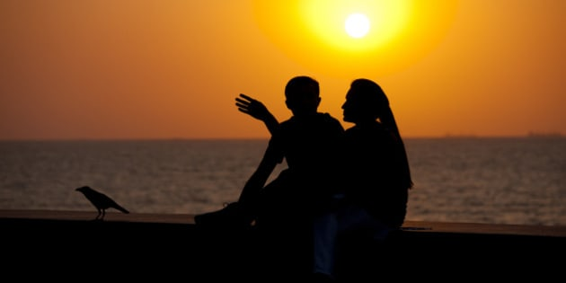 INDIA - MARCH 20:  Young Indian couple sit on seawall at sunset at Nariman Point, Mumbai, formerly Bombay, India  (Photo by Tim Graham/Getty Images)