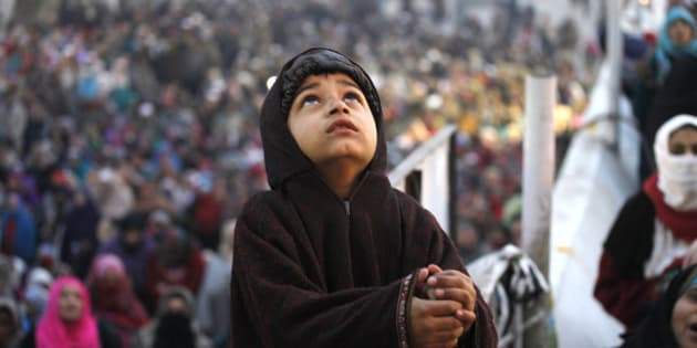 SRINAGAR, INDIA - JANUARY 4: A Kashmiri child devotee prays as a head priest display a holy relic of islam's prophet Muhammad on Eid Milad Un-Nabi, the birth anniversary of the prophet, at the Hazratbal shrine on January 4, 2015, in Srinagar, India. Celebrated on the 12th day of Rabi-ul-Awwal, the third month of the Islamic calendar, Eid Milad commemorates the birth anniversary of Prophet Mohammad. Hundreds of devout Muslims took part and offered special prayers for continuous peace, prosperity, progress and development of the country. (Photo by Waseem Andrabi/Hindustan Times via Getty Images)