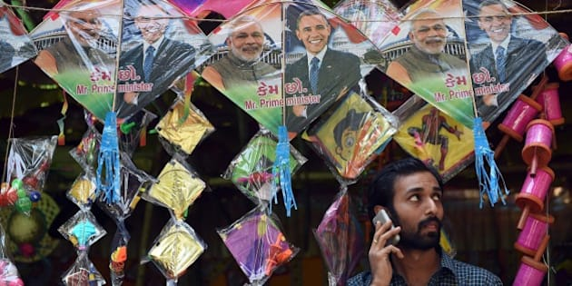 An Indian shopkeeper talks on his mobile phone below kites with images of Indian prime minister Narendra Modi (L) and US President Barack Obama (R) in Mumbai on January 7, 2015.  Obama travels to India as chief guest for the January 26, Republic Day celebrations and talks with Prime Minister Narendra Modi.  Modi has been courted by the United States as a key partner in its attempt to rebalance US diplomatic weight toward Asia.  AFP PHOTO / INDRANIL MUKHERJEE        (Photo credit should read INDRANIL MUKHERJEE/AFP/Getty Images)