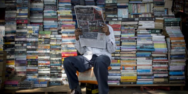 A book vendor reads a newspaper in Mumbai, India, on Tuesday, Nov. 6, 2012. Reserve Bank of India Governor Duvvuri Subbarao lowered the RBI's forecast for India's gross domestic product growth in the year through March to 5.8 percent, the slowest in almost a decade, from 6.5 percent. Photographer: Brent Lewin/Bloomberg via Getty Images