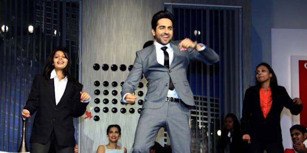 Indian Bollywood actors Ayushmann Khurrana (C) and Sonam Kapoor (2nd L, background) participate in a promotional event for the forthcoming Hindi film 'Bewakoofiyaan' in Mumbai on March 12, 2014. AFP PHOTO/STR        (Photo credit should read STRDEL/AFP/Getty Images)