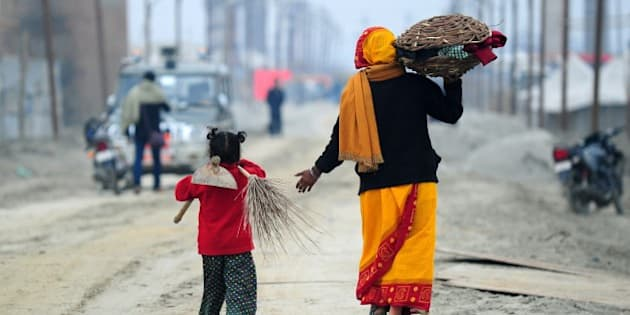 Young Indian child Laxmi (L) carries a broom and hoe as she walks with her mother after working at the site of the annual traditional fair Magh Mela at Sangam, the confluence of the rivers Ganges and Yamuna, and the mythical Saraswati in Allahabad on January 2, 2015. The Magh Mela which is known as a mini-Kumbh Mela is scheduled to start January 5 and continue until February 17 with auspicious bathing dates throughout the 45 day period.    AFP PHOTO/SANJAY KANOJIA        (Photo credit should read Sanjay Kanojia/AFP/Getty Images)