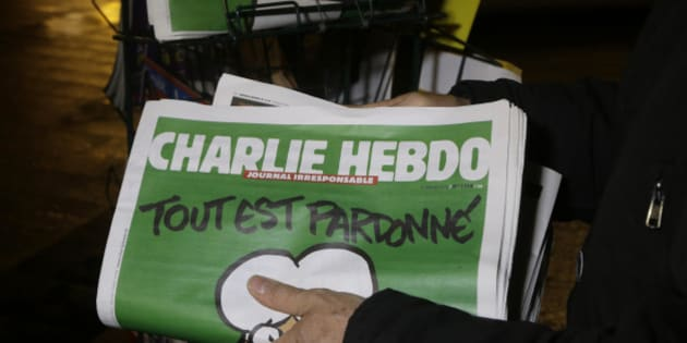 "A seller of newspapers installs in shelf, several Charlie Hebdo newspapers at a newsstand in Nice southeastern France, Wednesday, Jan. 14, 2015. On front page reading ""All is forgiven"". Charlie Hebdo's defiant issue is in print, with a caricature of the Prophet Muhammad on the cover and a double-page spread claiming that more turned out Sunday to back the satirical weekly ""than for Mass."" Twelve people died when two masked gunmen assaulted the newspaper's offices on Jan. 7, including much of the editorial staff and two police. (AP Photo/ Lionel Cironneau)"