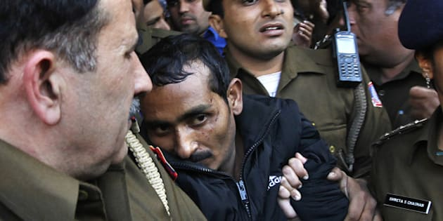 NEW DELHI, INDIA  DECEMBER 8: Police escort Uber cab driver Shiv Kumar Yadav (C, in black) who is accused of raping a woman, following his court appearance at the Tis Hazari court on December 8, 2014 in New Delhi, India. Shiv Kumar Yadav was remanded in custody for three days while police investigates the case. Delhi government banned Uber from operating in the Indian capital for failing to do background check on Shiv Kumar, who had previously been accused of assault. (Photo by Raj K Raj/Hindustan Times via Getty Images)