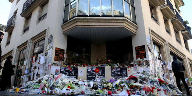 PARIS, FRANCE - JANUARY 14: People put flowers outside the Charlie Hebdo magazine office to commemorate the victims killed in a terrorist attack in the Rue Nicolas-Appert of Paris, France on January 14, 2015. (Photo by Mehmet Kaman/Anadolu Agency/Getty Images)