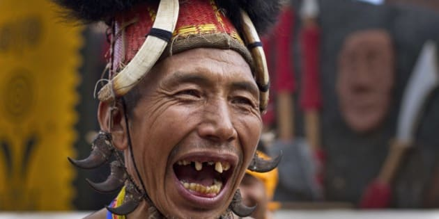 A Naga tribal man in traditional attire laughs as he waits to perform a dance during the Hornbill festival at the Kisama village in Nagaland, India, Tuesday, Dec. 2, 2014. The 10-day long festival named after the Hornbill bird is one of the biggest festivals of India's northeast that showcases the rich tradition and cultural heritage of the indigenous Nagas. (AP Photo/Anupam Nath)