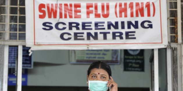 An Indian woman, wearing a mask, talks on her mobile phone outside the H1N1 swine flu screening centre at the Government Gandhi Hospital in Hyderabad on August 7, 2010. Health authorities confirmed that 15 more persons have tested positive for Swine Flu in the twin cities area of Hyderabad, local reports said. Six out of 21 nurses admitted to the hospital have tested positive for H1N1. AFP PHOTO/Noah SEELAM (Photo credit should read NOAH SEELAM/AFP/Getty Images)