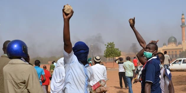People holds rocks as they demonstrate against French weekly Charlie Hebdo's publication of a cartoon of the Prophet Mohammed near the grand mosque in Niamey, on January 17, 2015.  At least 1,000 youths assembled at the grand mosque in the capital Niamey, some of them throwing rocks at police while others burned tyres and chanted 'Allahu Akbar' ('God is Greatest'). The protest came a day after a policeman and three civilians were killed and 45 injured in protests against Charlie Hebdo in Niger's second city of Zinder, which saw three churches ransacked and the French cultural centre burned down.