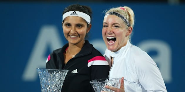 SYDNEY, AUSTRALIA - JANUARY 16: Bethanie Mattek-Sands of the USA and Sania Mirza of India pose with the trophy after victory in Women's Doubles Final Match against Raquel Kops-Jones and Abigail Spears of the USA during day six of the 2015 Sydney International at Sydney Olympic Park Tennis Centre on January 16, 2015 in Sydney, Australia.  (Photo by Brendon Thorne/Getty Images)