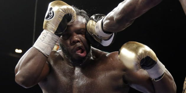 Bermane Stiverne takes a punch from Deontay Wilder during their WBC heavyweight championship boxing match Saturday, Jan. 17, 2015, in Las Vegas. Wilder won by unanimous decision. (AP Photo/Isaac Brekken)
