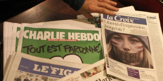 """Copies of the latest issue of Charlie Hebdo newspaper are sold with other newspapers at a newsstand in Lille, northern France, Wednesday, Jan. 14, 2015. In an emotional act of defiance, Charlie Hebdo resurrected its irreverent and often provocative newspaper, featuring a caricature of the Prophet Muhammad on the cover that drew immediate criticism and threats of more violence. The black letters on the front page read: """"All is forgiven."""" (AP Photo/Michel Spingler)"""