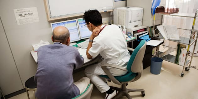 Kojiro Tokutake, a gastroenterologist at Nagano Prefectural Suzaka Hospital, right, discusses diagnostic test results with a patient at the hospital in Suzaka, Nagano Prefecture, Japan, on Friday, Nov. 8, 2013. Tokutake wanted to be a doctor since he was a teenager. His grandmother bought him his first stethoscope when he was in medical school. A decade later, he helped her die. Photographer: Ko Sasaki/Bloomberg via Getty Images
