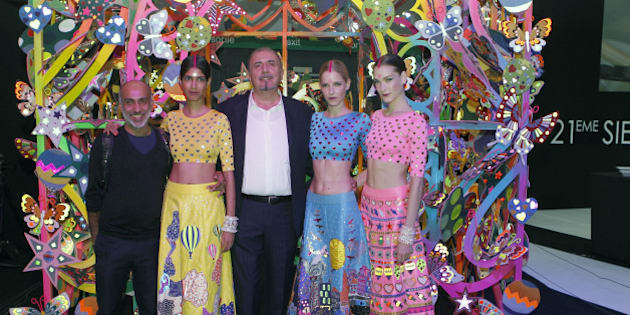 PARIS, FRANCE - OCTOBER 02: Indian designer Manish Arora and Alcantara CEO, Andrea Boragno poses with models in a fantasy house titled 'Life is Beautiful' created by Manish Arora after a fashion show during the Paris Motor Show on October 02, 2014 in Paris, France. Alcantara CEO, Andrea Boragno has set up an exceptional collaboration with Manish Arora.  (Photo by Chesnot/Getty Images)